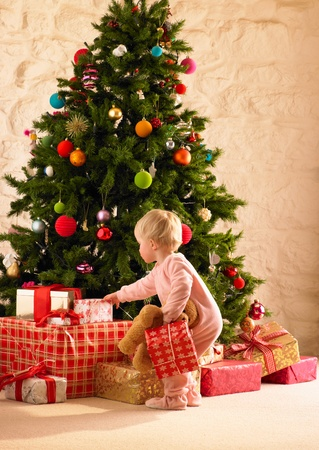 Little girl with parcels round Christmas tree photo