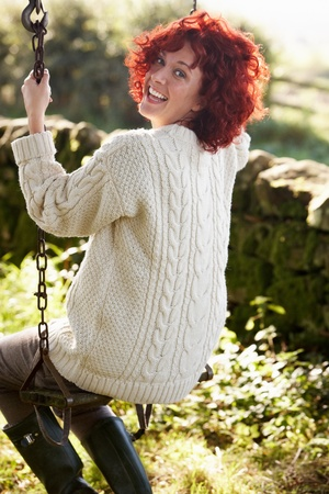 Woman on country garden swing photo