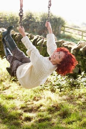 Femme sur la balançoire de jardin pays