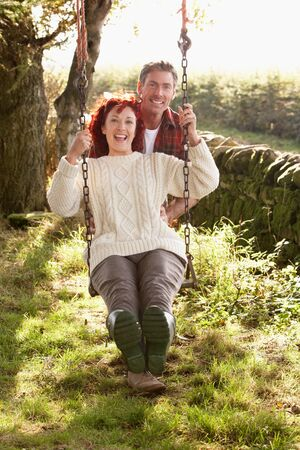 swinging: Couple with country garden swing