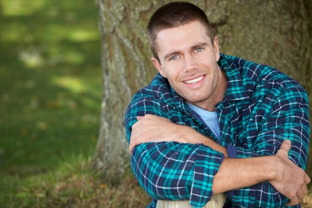 Man sitting against tree trunk Stock Photo