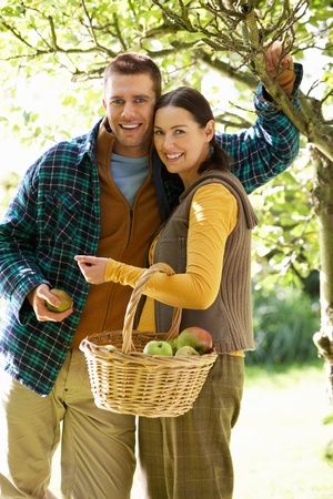 Couple picking apples in garden photo