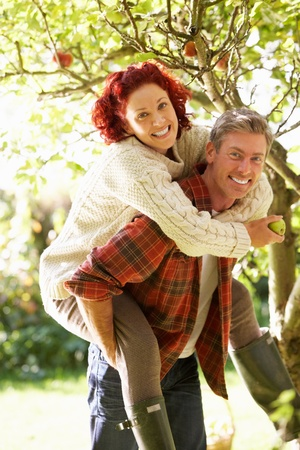 Couple picking apples off tree photo