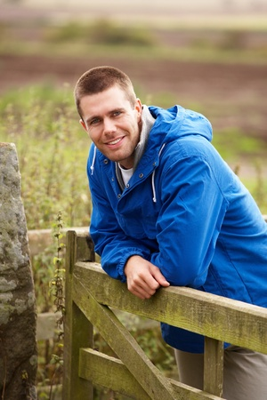 rugged: Man leaning on country gate Stock Photo