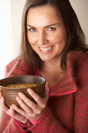 30s: Woman holding bowl of soup