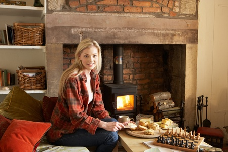 Young woman having tea by fire Stockfoto
