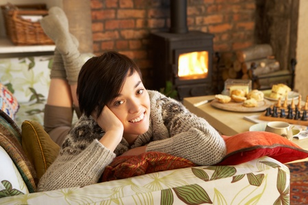 Young woman relaxing by fire photo