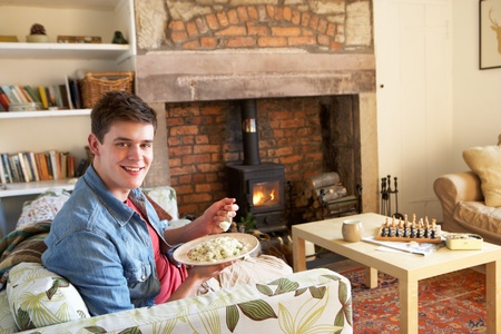 Young man eating meal by fire photo
