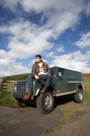 Jeune homme dans la campagne avec SUV