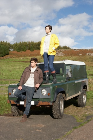 Young couple in countryside with SUV photo