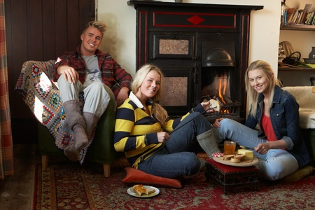 making a fire: Young adults making toast on open fire Stock Photo