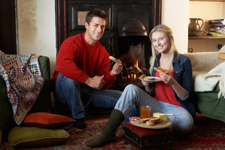 Young couple making toast on open fire photo