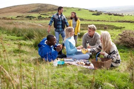 assis par terre: Les jeunes adultes sur pique-nique champ�tre Banque d'images