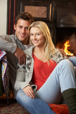 Young couple sitting by open fire Stockfoto