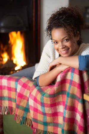 Young woman sitting by open fire photo