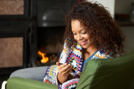 Young woman sitting by fire with phone photo