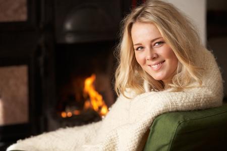 Junge Frau sitzt am offenen Feuer