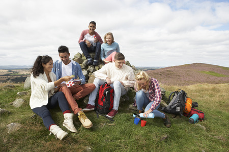 old man sitting: Group Of Young People Hiking In Countryside Stock Photo