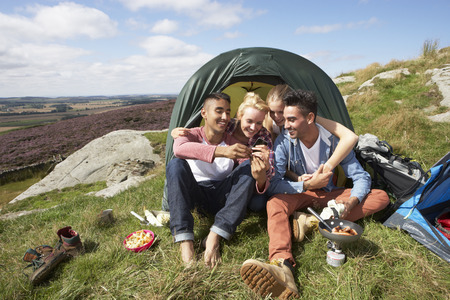 Group Of Young People Checking Mobile Phone On Camping Trip photo