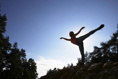 Silhouette Of Teenage Girl Balancing On Rock photo