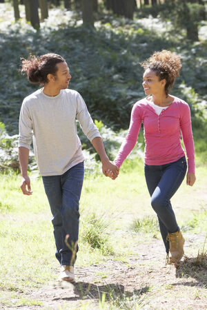 mixed races: Romantic Young Couple Walking In Countryside Stock Photo