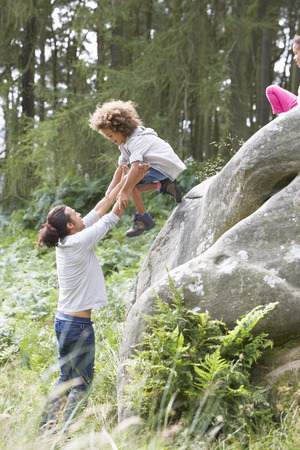 helping children: Father Helping Children To Jump Off Rocks Stock Photo