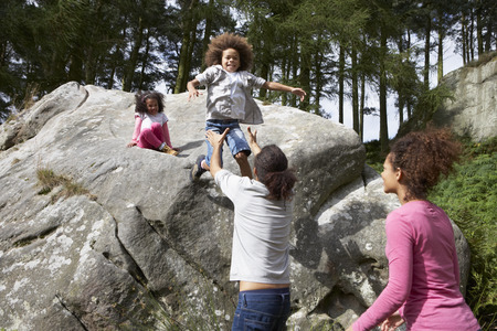 outdoor pursuit: Father Helping Children To Jump Off Rocks Stock Photo