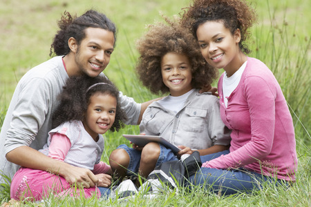 mixed race family: Family Using Digital Tablet Whilst Hiking In Countryside