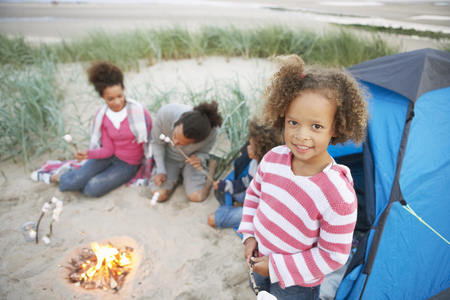 5 year old girl: Family Camping On Beach And Toasting Marshmallows Stock Photo