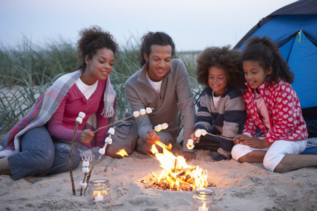 camping: Family Camping On Beach And Toasting Marshmallows Stock Photo