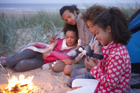 Family Camping On Beach And Toasting Marshmallows Standard-Bild