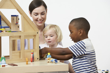 Pre-School Teacher And Pupils Playing With Wooden House Stock Photo