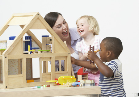 Pre-School Teacher And Pupils Playing With Wooden House photo