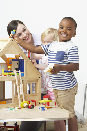 pre schooler: Pre-School Teacher And Pupils Playing With Wooden House Stock Photo