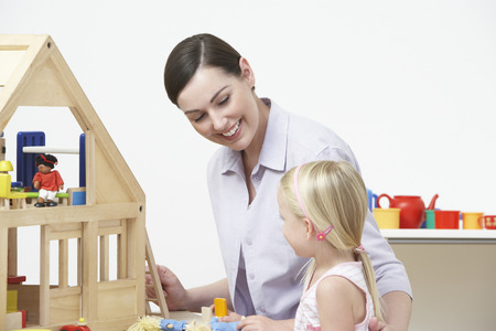 preschool: Pre-School Teacher And Pupil Playing With Wooden House
