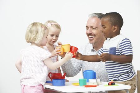 pre schooler: Pre School Children Enjoying Tea Party With Teacher Stock Photo