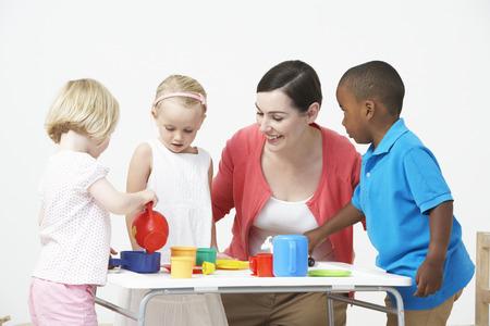 Pre School Children Enjoying Tea Party With Teacher Stock Photo