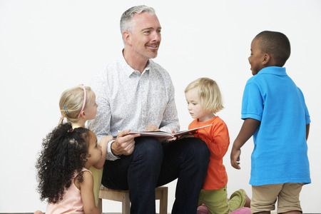 pre schooler: Pre School Teacher Reading Story To Children