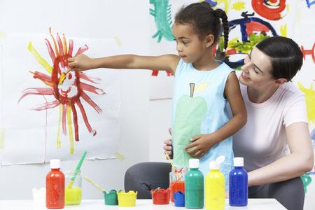 Teacher And Pupil In Pre School Art Class photo