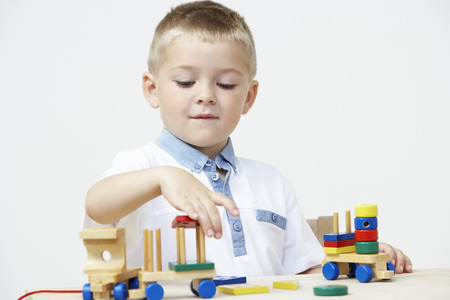 pre schooler: Pre-School Pupil Playing With Wooden Toy Train
