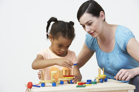 pre schooler: Teacher And Pre-School Pupil Playing With Wooden House