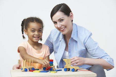 Teacher And Pre-School Pupil Playing With Wooden House photo