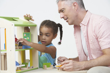 pre schooler: Pre-School Teacher And Pupil Playing With Wooden House