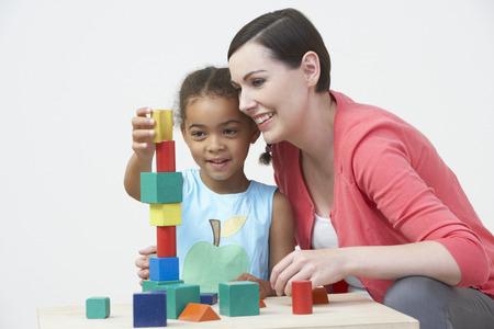 profesor alumno: Profesor Y Pre-School Pupil juega con los bloques de madera Foto de archivo