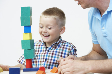 old building: Teacher And Pre-School Pupil Playing With Wooden Blocks