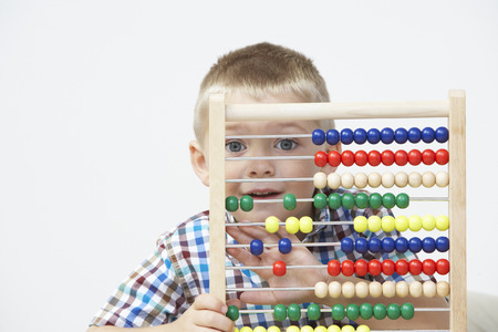 pre schooler: Studio Shot Of Boy Playing With Abacus
