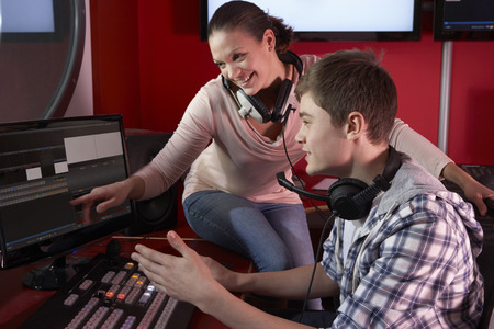college student: Media Student With Tutor Working In Film Editing Class Stock Photo