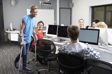crutch: Male Pupil Walking On Crutches In Computer Class
