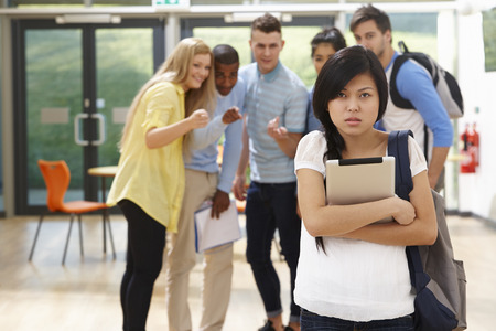 unkind: Female Student Being Bullied By Classmates Stock Photo