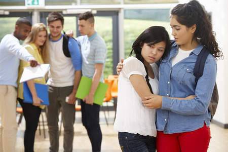 unkind: Friend Comforting Victim Of Bullying At School Stock Photo